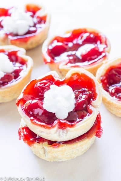 Several round mini cherry pies with a dollop of whipped cream