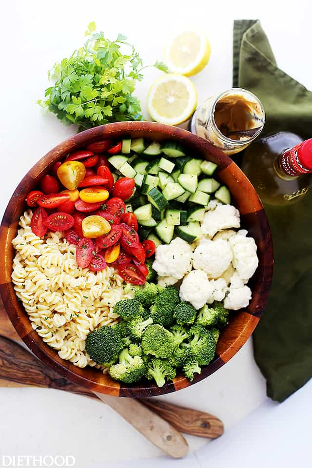 A large wooden bowl with pasta, tomatoes, broccoli, cauliflower and cucumbers