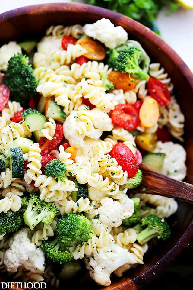 A close up of pasta salad that has broccoli, cauliflower, tomatoes and cucumbers in it