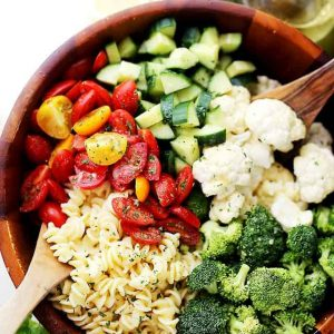 Potluck Pasta Salad with Dijon Vinaigrette - Quick and easy to make Potluck Pasta Salad packed with broccoli, tomatoes, cucumbers and cauliflower, all tossed in a zesty and delicious homemade Dijon Vinaigrette!