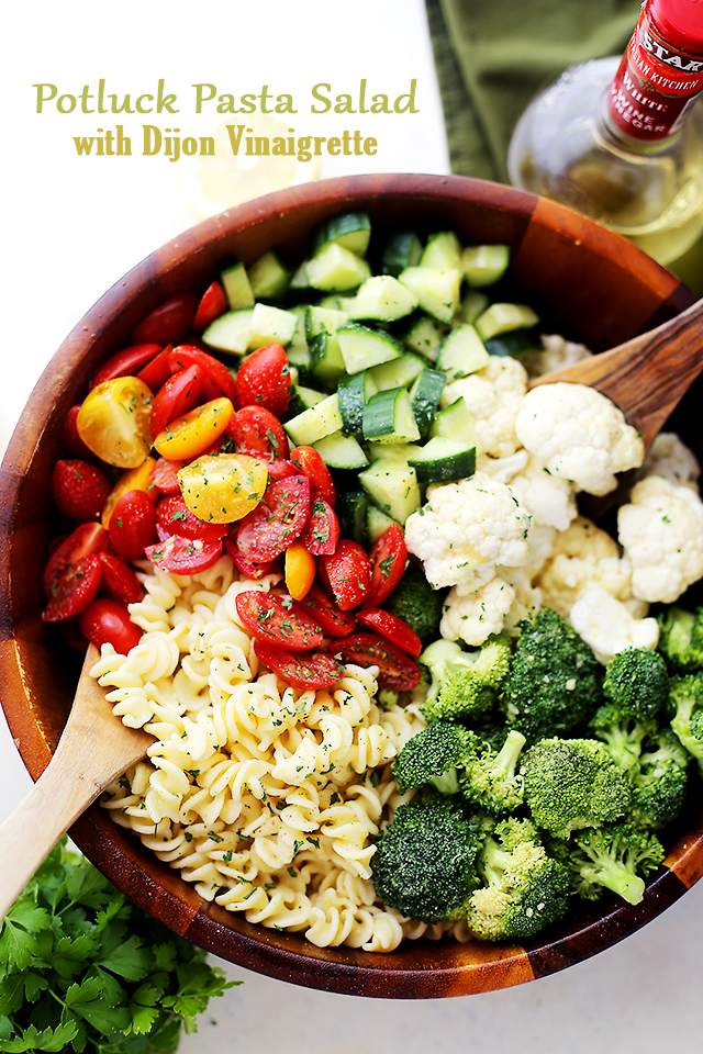 A wooden bowl filled with fresh tomatoes, cucumbers, broccoli, cauliflower and pasta separated into sections