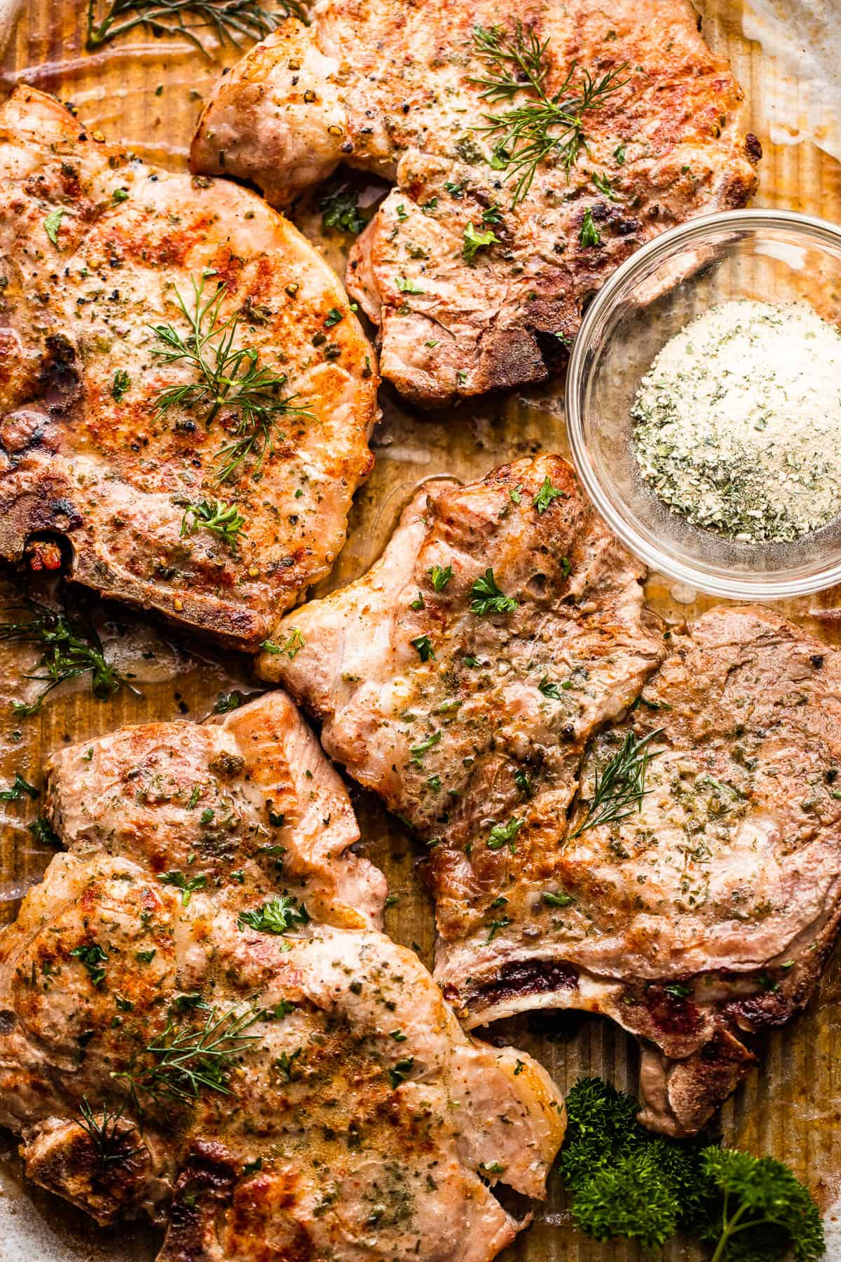 tray with four ranch seasoned pork chops with ranch seasoning in a small mixing bowl
