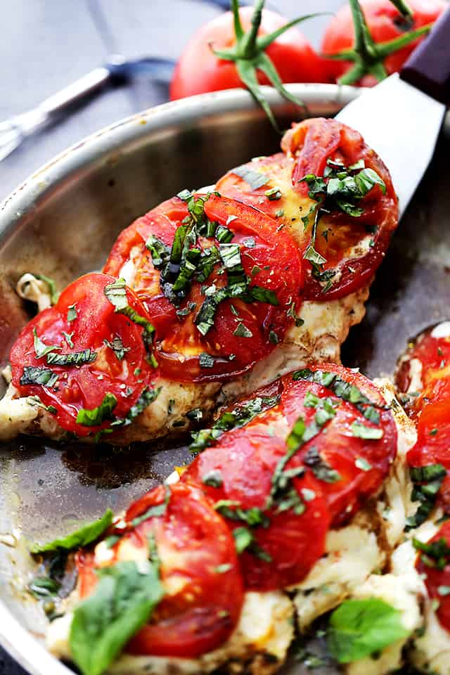 Caprese Chicken in a skillet with a spatula.