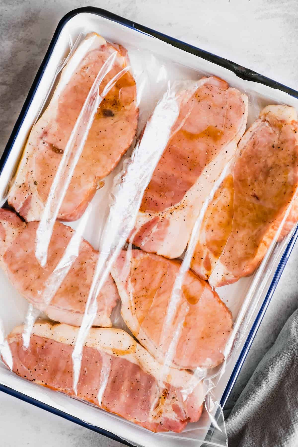 6 pork chops on a tray with marinade.