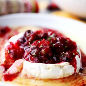 A wheel of melted baked brie cheese topped with red cranberry sauce.