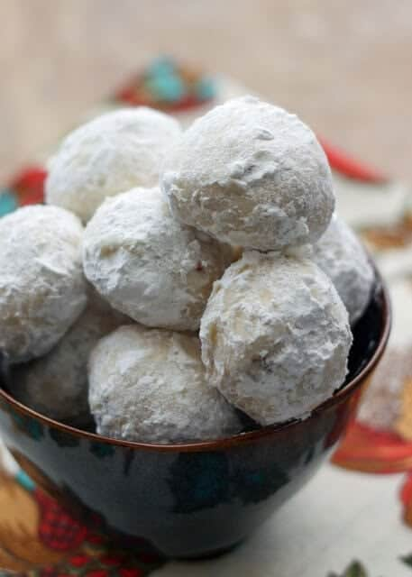 A pile of Mexican Wedding Cookies topped with powdered sugar in a bowl