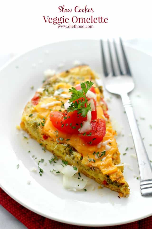 A slice of slow cooker veggie omelette with tomatoes on a plate