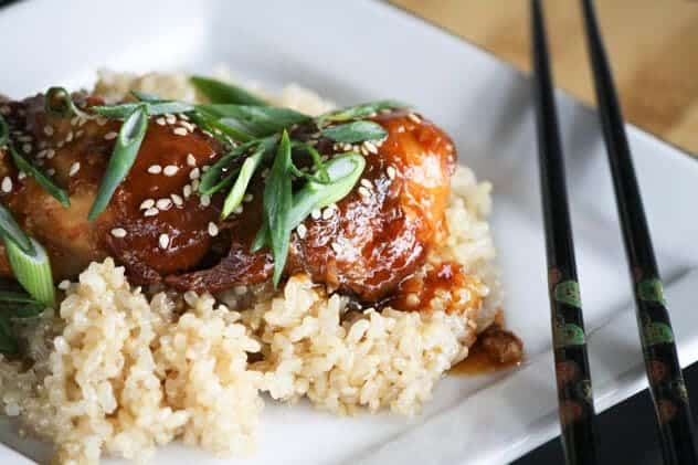 Slow Cooker Honey Sesame Chicken over rice with fresh herbs