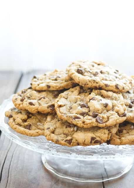 A pile of salted chocolate chip cookies on a pedestal serving dish