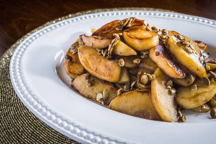 Browned Butter Roasted Apples with toasted pumpkin seeds on a plate