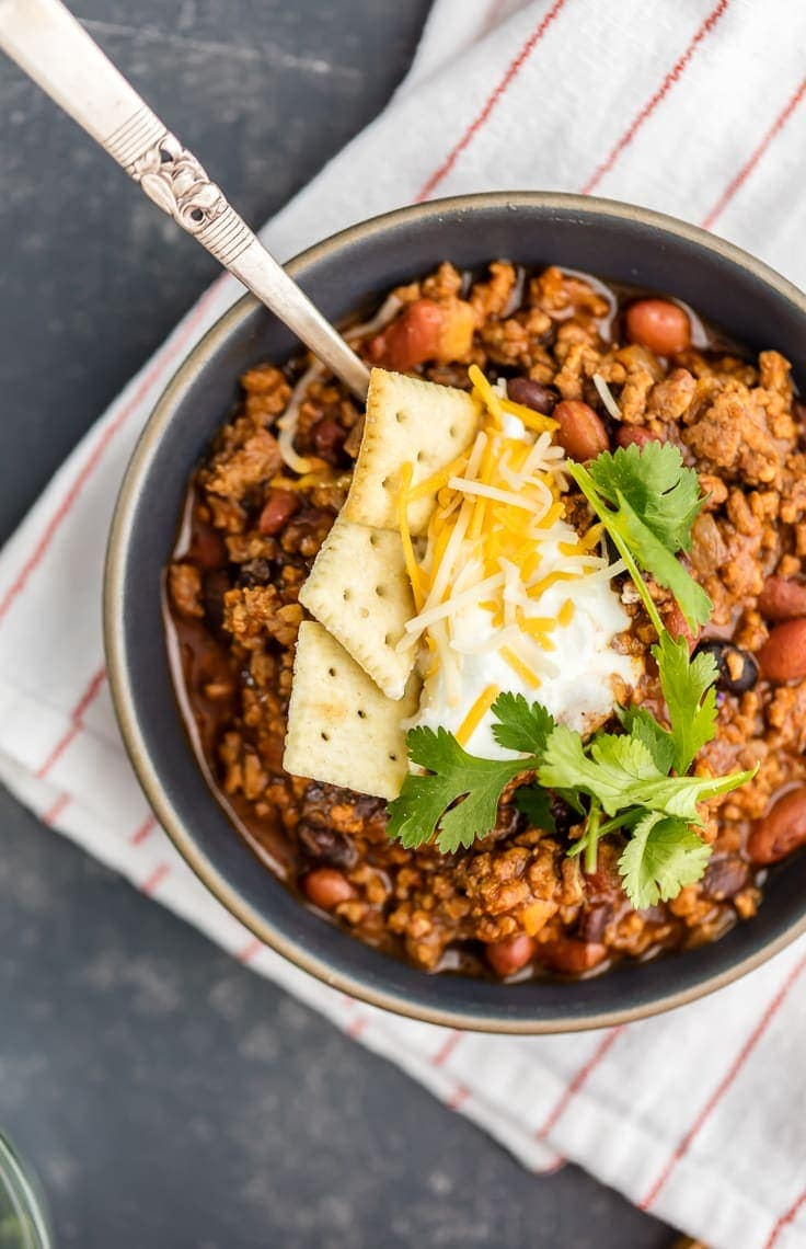 A bowl of chili topped with crackers, sour cream, cheese and fresh herbs