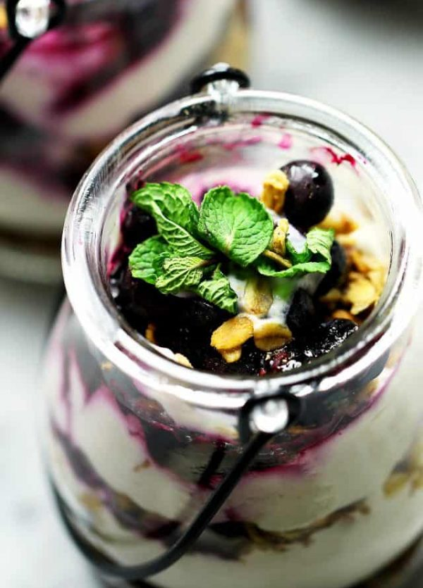 No Bake Skinny Blueberry Cheesecake Parfaits - Delicious layers of lightened-up creamy and lemony cheesecake filling, sweet granola, and a homemade blueberry sauce.