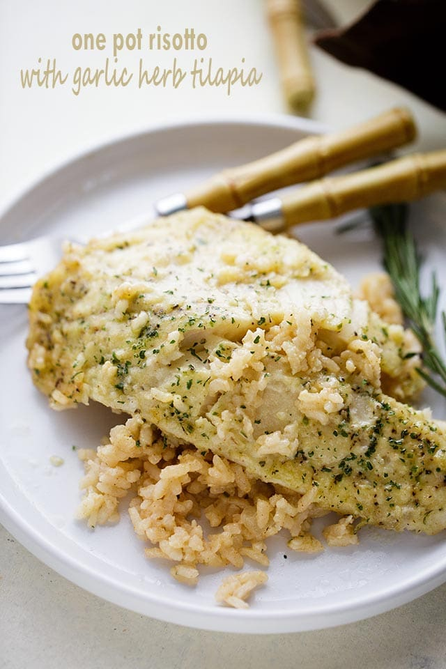 One Pan Risotto with Garlic Herb Tilapia - Delicious, garlicky Tilapia set over a flavorful bed of rice and baked to a creamy perfection!