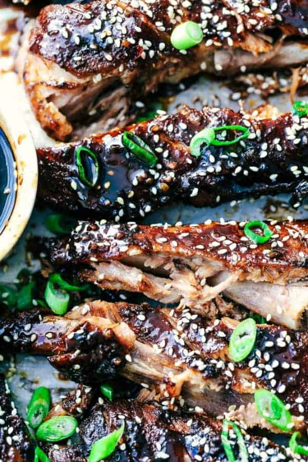 Slow Cooker Asian Sticky Ribs topped with sesame seeds and scallions