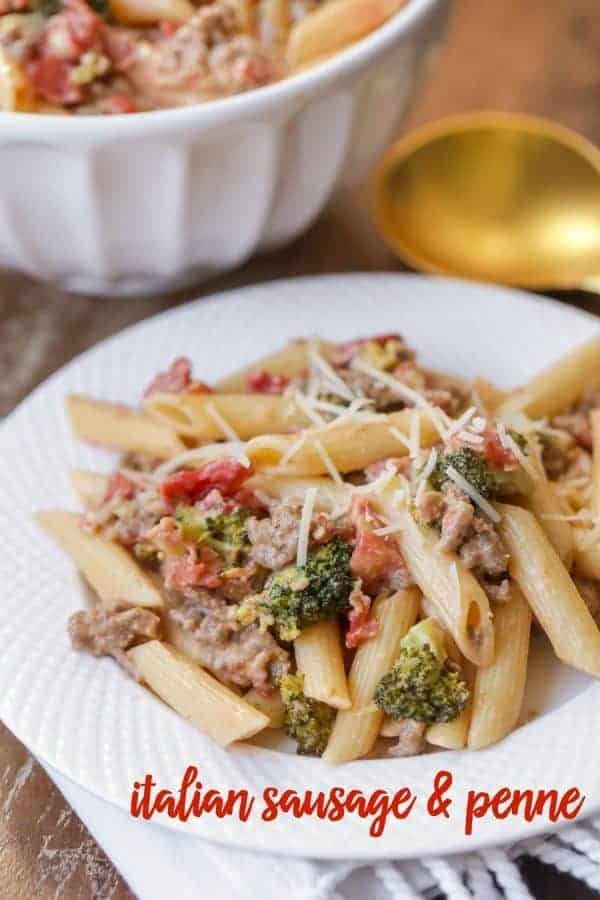 Italian Sausage and Penne with vegetables in a bowl topped with shredded parmesan