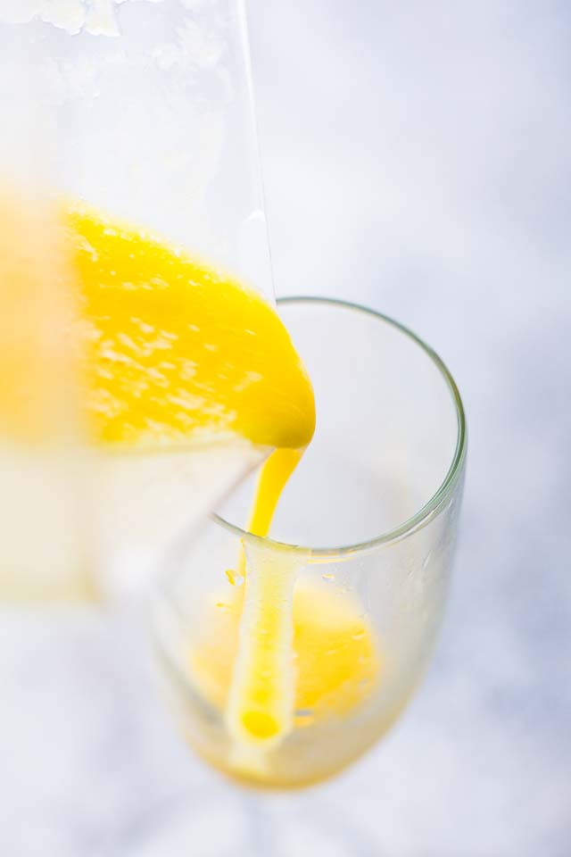 pouring mango puree in a champagne glass