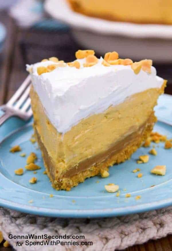 A slice of peanut butter pie with whipped cream topping on a plate