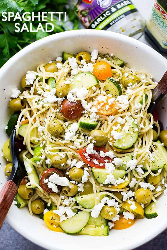 Spaghetti Salad in a salad bowl topped with tomatoes, cucumbers, olives, and cheese.
