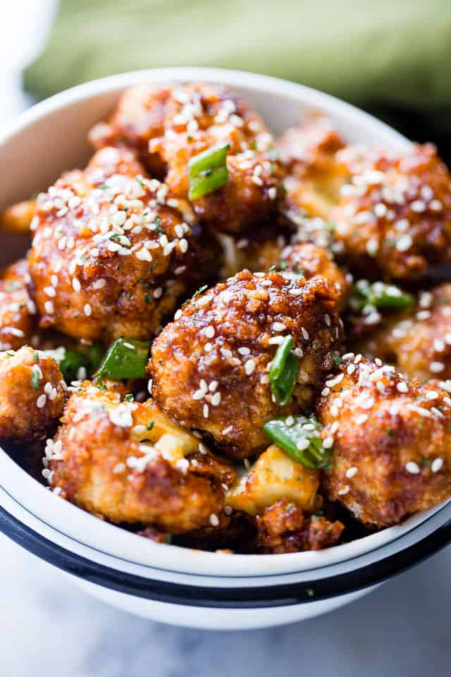Sticky Sesame Cauliflower Bites - Sweet, spicy, baked cauliflower bites topped with an amazing Asian-inspired sticky sauce! Serve them as finger food appetizers or as the main course over rice for a delicious veggie dinner.