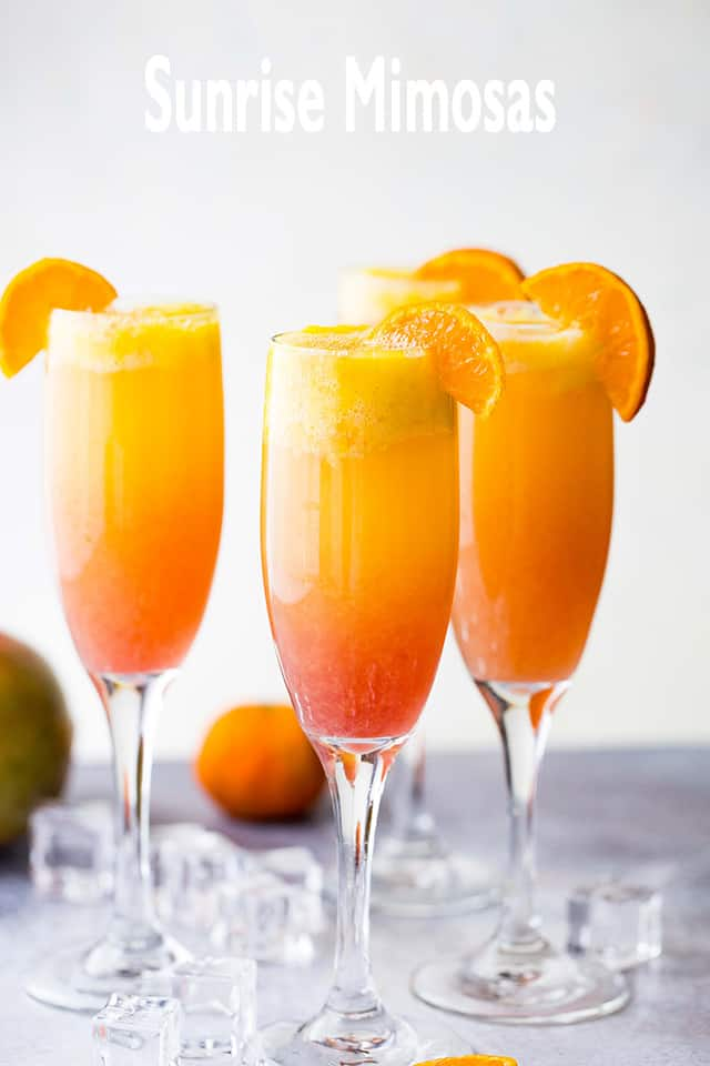 Sunrise Mimosas served in 3 champagne glasses.