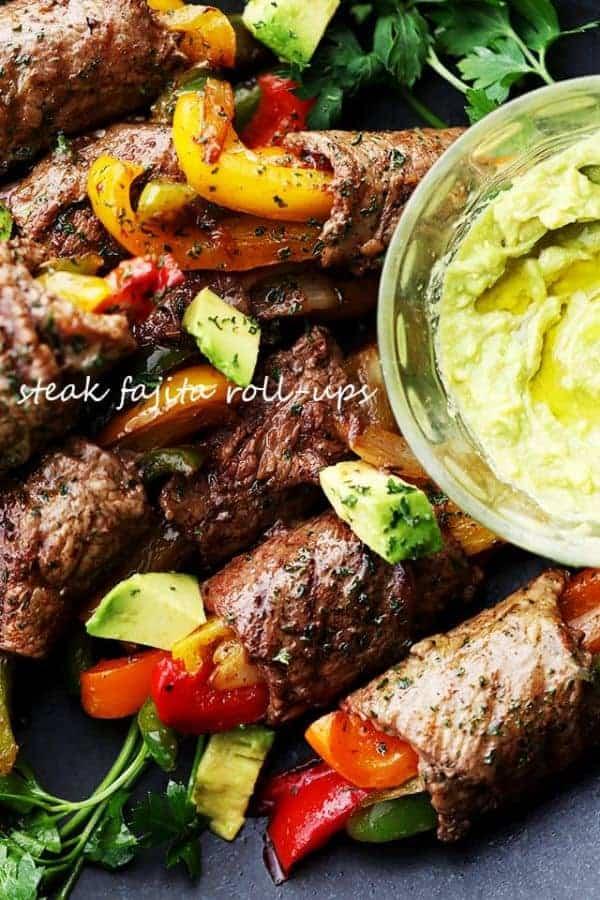 Steak fajita roll-ups on a plate with a cup of guacamole
