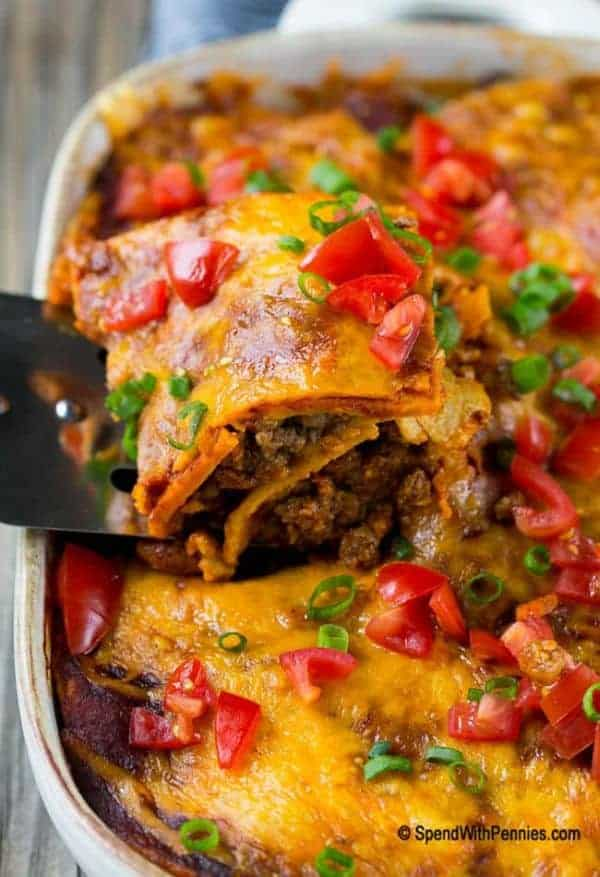 Beef enchilada casserole in a baking dish topped with melted cheese, tomatoes, and scallions