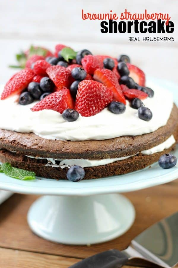 Two layered brownie strawberry shortcake with whipped cream and berries on a cake pedastal