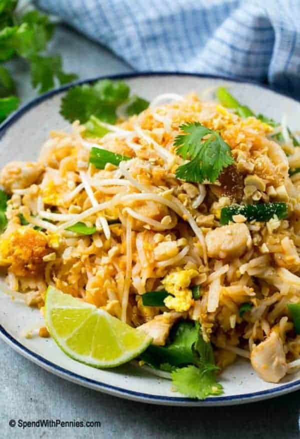 Chicken Pad Thai in a bowl garnished with fresh cilantro and a lime wedge