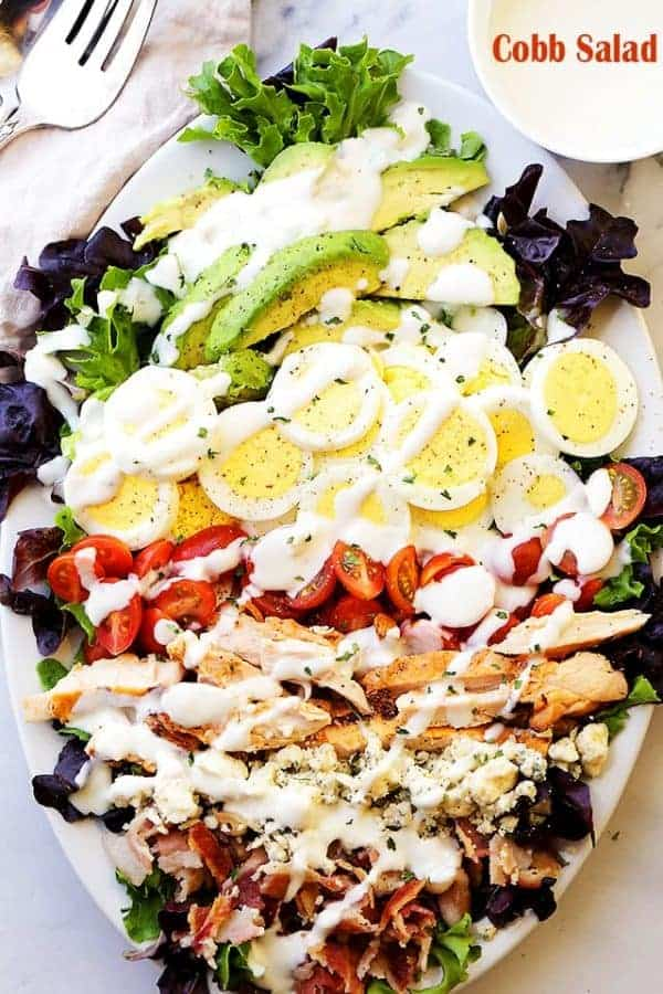 Top view of Cobb Salad with grilled chicken, tomato, egg, avocado and creamy dressing