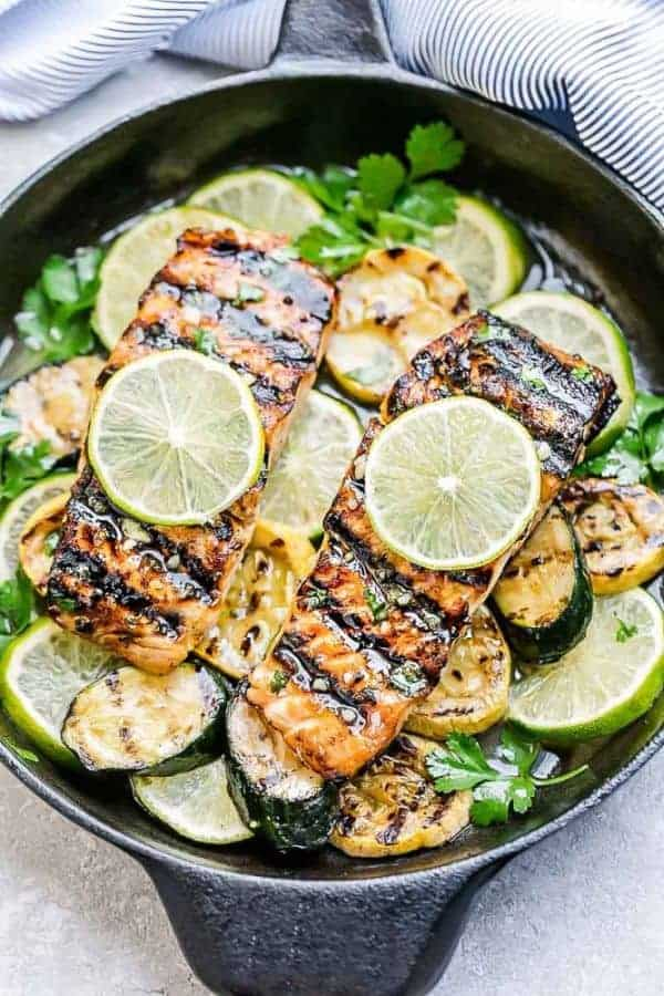 Two fillets of Grilled Honey Lime Salmon in a cast iron skillet with lime slices and fresh herbs