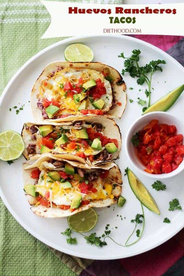 Top view of three Huevos Rancheros Tacos on a plate with avocado, lime and a cup of salsa