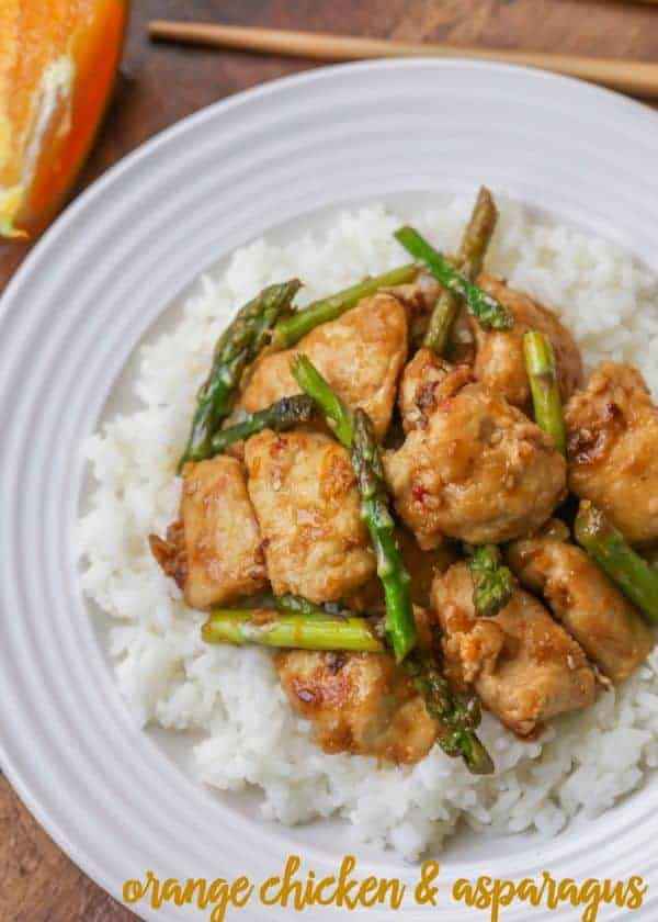 Orange chicken and asparagus over white rice on a plate