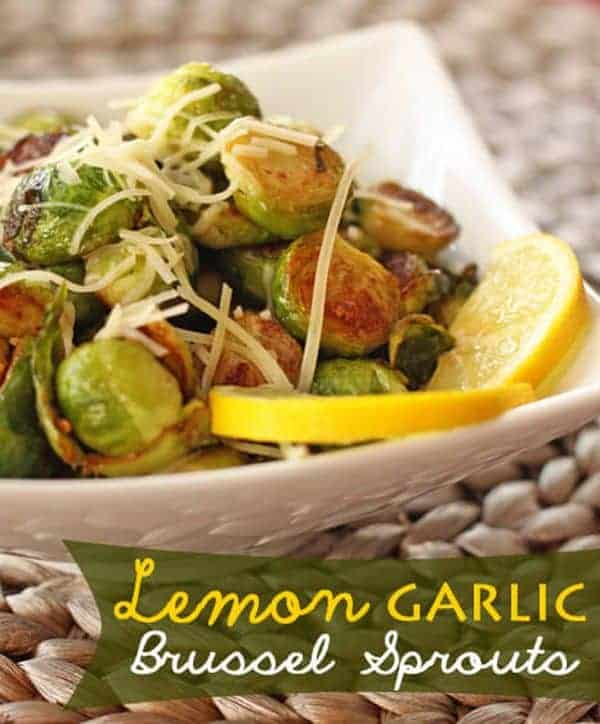 Lemon Garlic Brussels Sprouts in a square serving bowl with lemon slices and parmesan