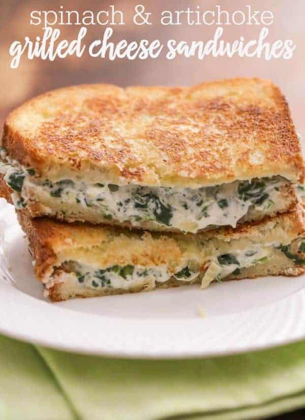 Two halves of Spinach Artichoke Grilled Cheese Sandwich stacked on a plate