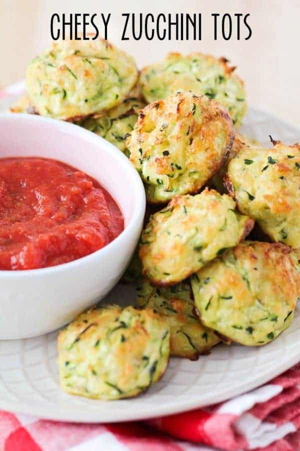 Cheesy Zucchini Tots on a plate with a bowl of marinara sauce