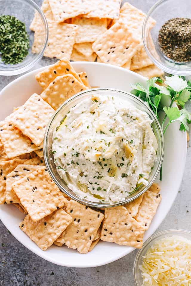 Light Creamy Artichoke Dip - My favorite dip to bring to Holiday parties! It's creamy, cheesy, yet light and super delicious!