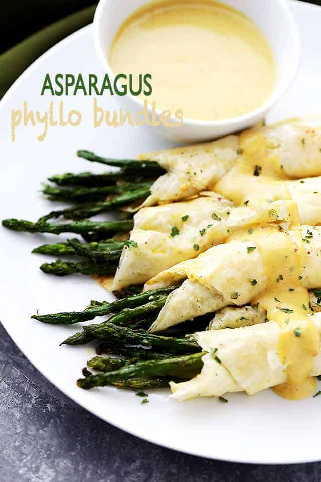 asparagus wrapped in phyllo and served on a white plate.