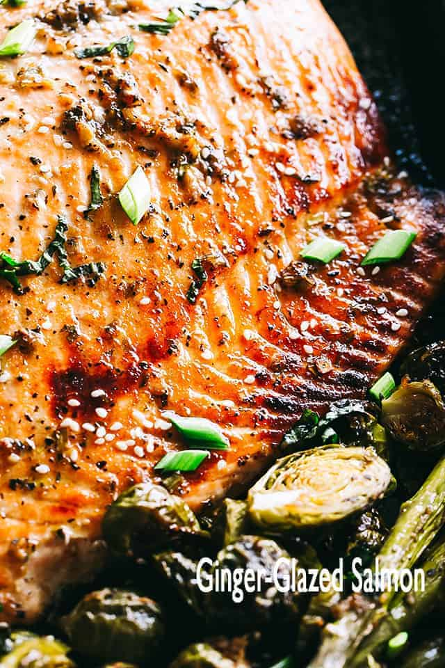 This irresistible baked salmon recipe is simple to prepare & ready in about 30 min! A sweet & spicy ginger-glaze makes this salmon recipe out of this world. #salmon #dinner