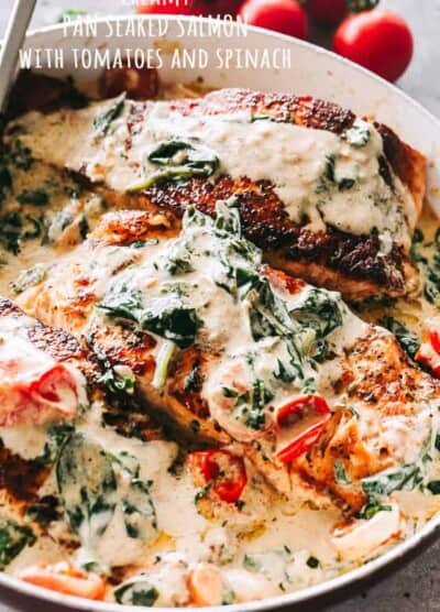 Pan Seared Salmon with Tomatoes and Spinach - Quick and easy pan-seared salmon is smothered in a flavorful creamless creamy sauce prepared with evaporated milk, tomatoes, and baby spinach.