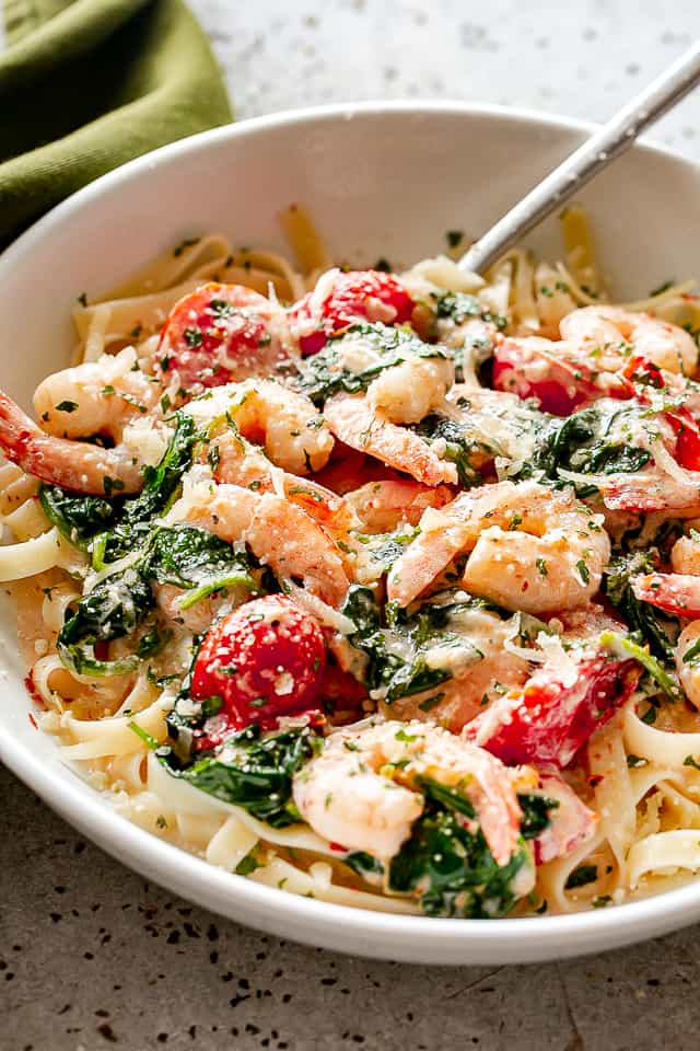 shrimp fettuccine with spinach and tomatoes.