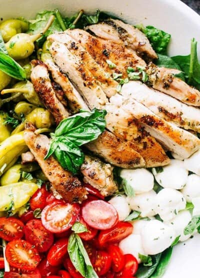 Antipasto Salad with Grilled Chicken and Basil Pesto Vinaigrette - Fresh and delicious salad packed with grilled chicken, mozzarella cheese, tomatoes, and pepperoncini, all tossed in an amazing homemade Basil Pesto Vinaigrette.