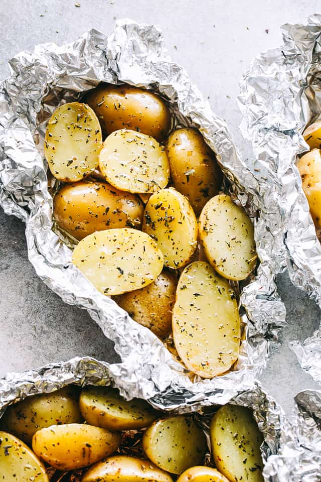 Garlic Herb Grilled Potatoes in Foil - A good dose of garlic, thyme, and rosemary make these potatoes that much more delicious, and the grill gives them just the right amount of crispness and a delicious smoky flavor.