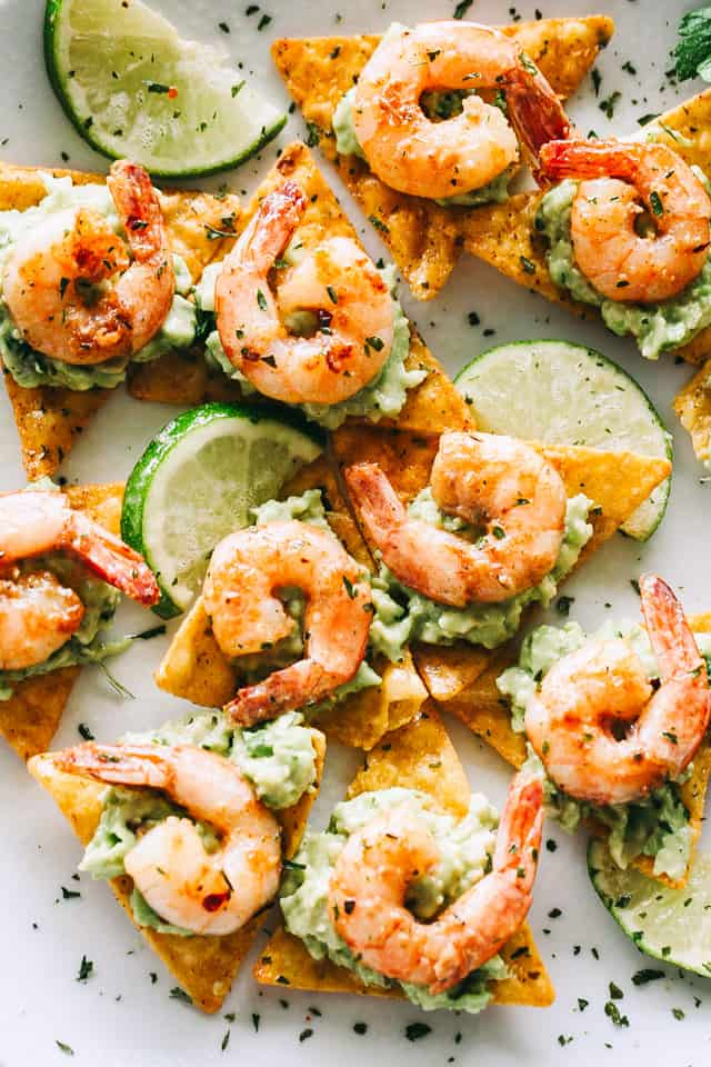 Cajun Shrimp and Guacamole Tortilla Bites - Crispy tortilla chips topped with guacamole and the best tender and juicy cajun shrimp! Super easy and delicious appetizer that's perfect for summer cookouts or game day parties.