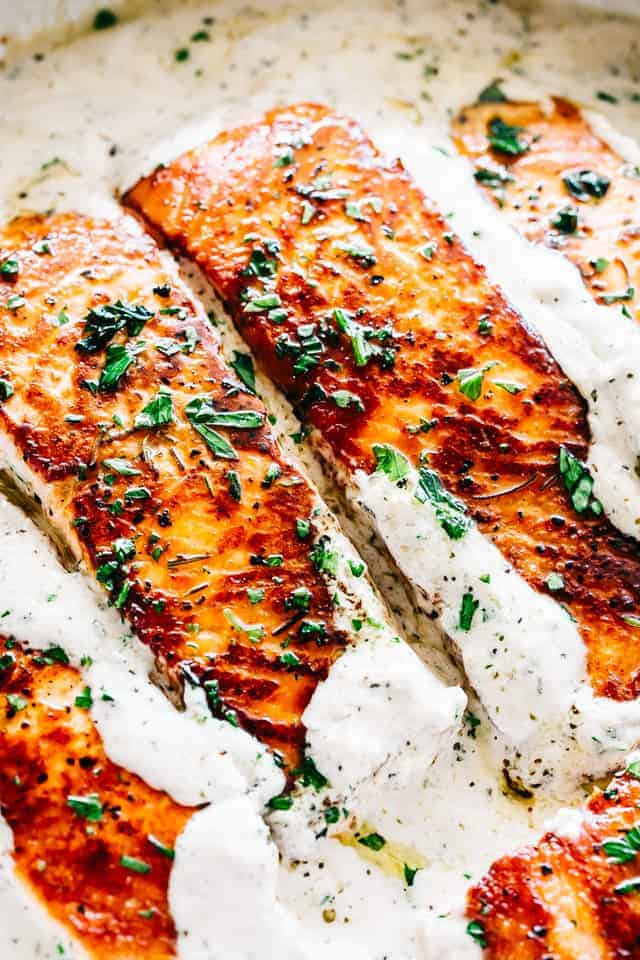 One skillet salmon dinner served with lemon garlic cream sauce.Quick enough for a weeknight dinner & so good it's sure to become a favorite salmon recipe. #salmon #dinner