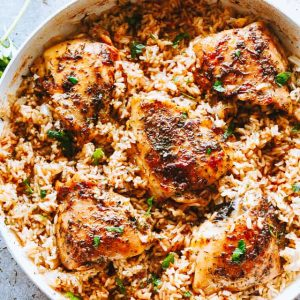 Garlic Butter Chicken and Rice Recipe - Bursting with rich buttery garlic flavor and tender chicken thighs, this is a one pot chicken and rice dinner guaranteed to impress even the pickiest eaters!