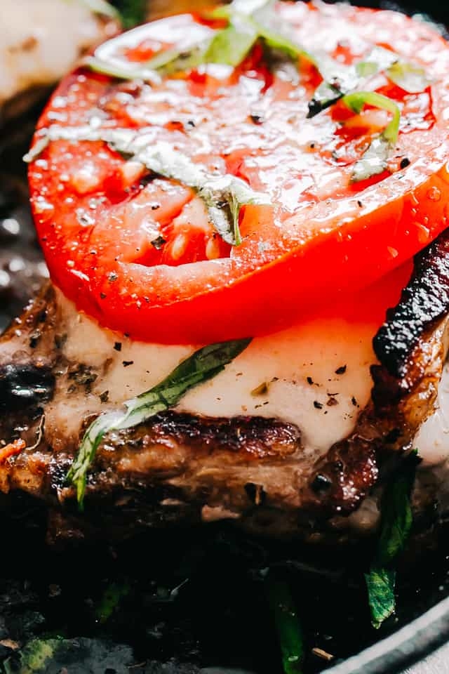 Caprese Pork Chops - Seared juicy caprese pork chops marinated in a garlicky balsamic glaze and topped with sweet tomatoes, melted mozzarella cheese, and fresh basil!