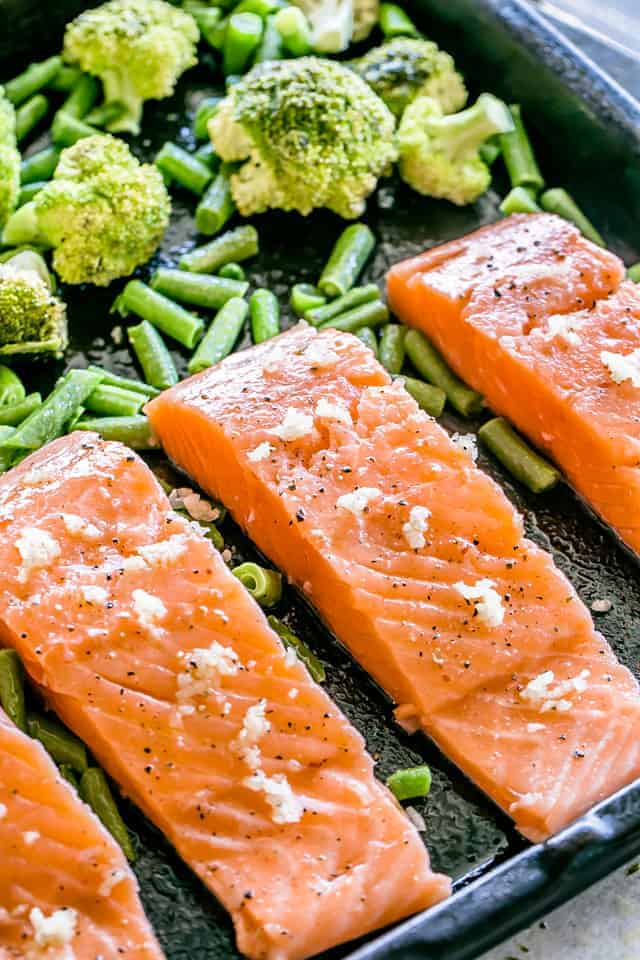Raw salmon on a sheet pan with veggies