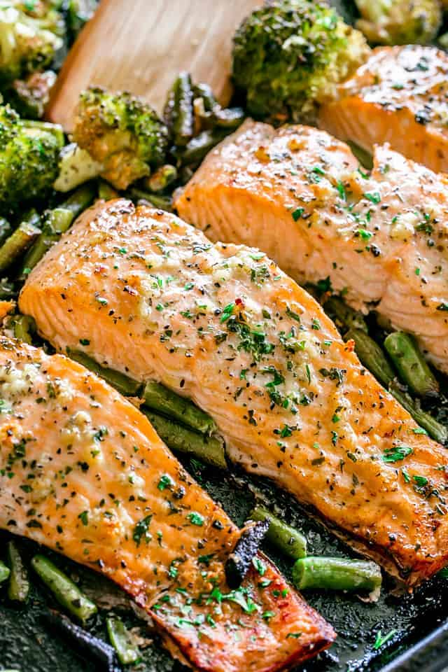 Garlic Butter Baked Salmon - Tender and juicy salmon brushed with an incredible garlic butter sauce and baked on a sheet pan with your favorite veggies. This delicious baked salmon takes just a few minutes of prep and makes for a perfect weeknight meal in just 30 minutes.