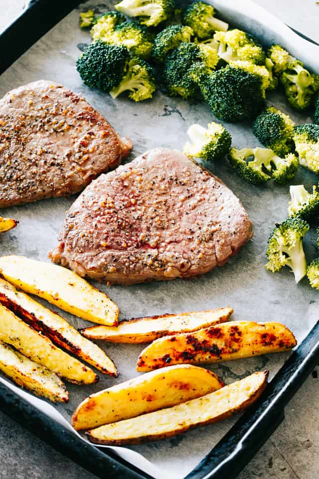 Sheet Pan Steak and Shrimp Dinner - The classic Surf and Turf dinner prepared with melt-in-your-mouth tender steak and garlicky shrimp on just one sheet pan. Broccoli and potato wedges, included!