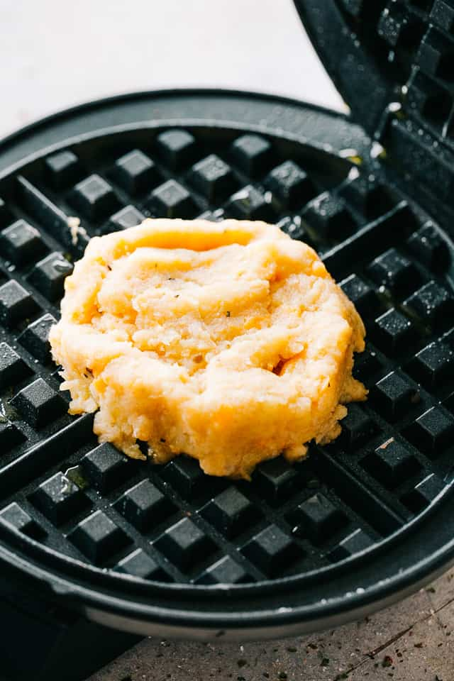 Cheesy Potato Waffles - Delicious, cheesy, and savory waffles prepared with leftover mashed potatoes and cheddar cheese. Crispy on the outside and fluffy on the inside, these potato waffles not only taste amazing, but they are a super fun meal to serve to your family.